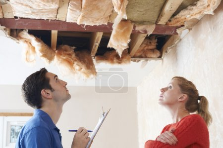 Builder And Client Inspecting Roof Damage