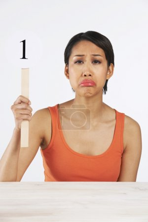 Sad Woman Holding Up Scorecard Giving Mark Out Of Ten