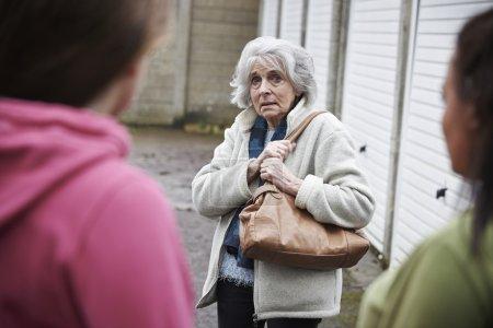 Photo pour Haute femme se sentir intimidés par les adolescentes - image libre de droit