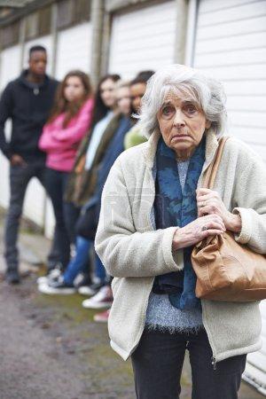Photo pour Haute femme se sentir intimidés par le groupe de jeunes - image libre de droit