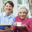Senior Woman With Carer At Home...