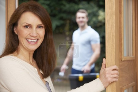 Woman Opening Door To Repair Man