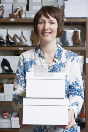 Female Owner Of Shoe Store Carrying Boxes