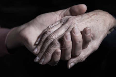 Young Woman Holding Old Woman's Hand Against Black...