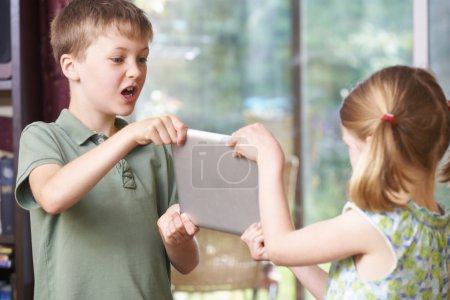 Boy And Girl Fighting Over Digital Tablet At Home