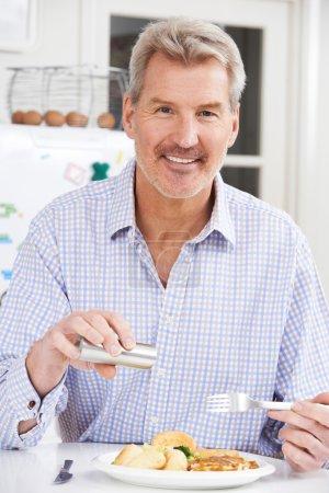 Photo pour Homme à la maison Ajouter du sel au repas - image libre de droit