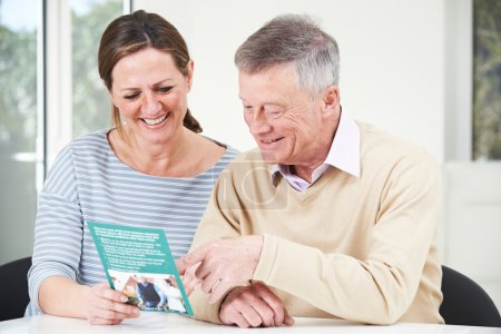 Senior Man With Adult Daughter Looking At Brochure...