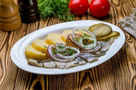 Photo pour Hareng aux pommes de terre sur plaque blanche - image libre de droit