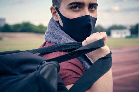 Photo pour Gros plan du jeune athlète avec sac à dos et masque de protection contre la pandémie de covidé-19. Concept de santé, sport, coronavirus pandémique mondial - image libre de droit