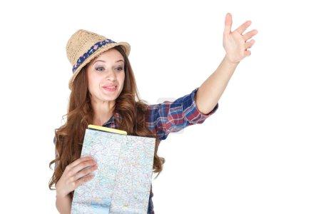 Photo pour Belle jeune touriste féminine étudiant une carte. la fille pointant la direction de la route. isolé sur fond blanc - image libre de droit