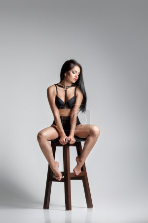 Photo for Sexy woman in black bodysuit on high chair posing in the Studio. - Royalty Free Image