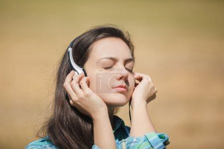 Photo pour Jeune fille de mode souriante avec écouteurs au champ de blé . - image libre de droit