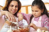 Mother and daughter prepare meat for lunch