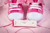 Těhotenský test s pozitivním výsledkem a oblečení pro novorozence, čeká miminko