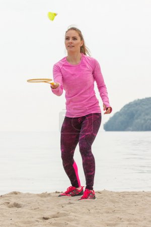 Happy smiling woman playing badminton at beach, active lifestyle