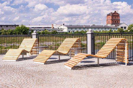 Konin, Poland - June 18, 2016: Lounge chairs for recreation on embankment of polish Warta river in town Konin