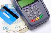 Platební terminál s kreditní kartou a peníze na bílém pozadí