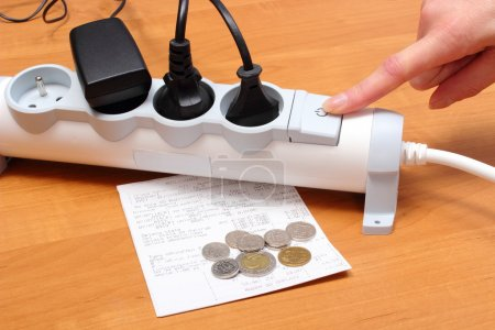 Electrical cords connected to power strip and electricity bill with coins