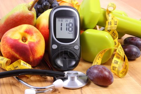 Glucose meter with medical stethoscope, fruits and dumbbells for using in fitness