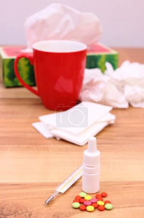 Pills and nose drops for colds, used handkerchiefs and hot tea with lemon