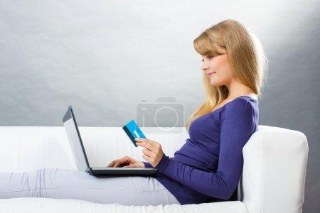 Photo pour Femme heureuse tenant une carte de crédit à l'aide d'un ordinateur portable assis sur le canapé, payant sur Internet pour les achats en ligne, tapant sur le clavier de l'ordinateur, surfant sur Internet - image libre de droit