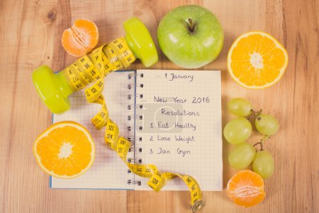 Vintage photo, New years resolutions written in notebook and dumbbells with centimeter