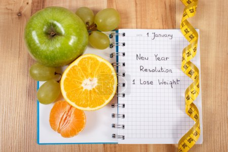 New years resolutions written in notebook and tape measure