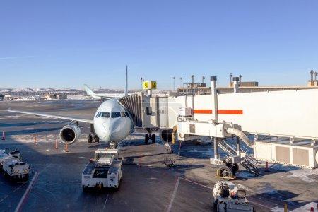 Photo pour Un avion de ligne, connecté à une passerelle d'embarquement étant confiée à la porte de l'aéroport. - image libre de droit