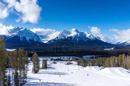 Photo pour Les skieurs et les snowboarders descendent les pistes de Lake Louise dans les Rocheuses canadiennes. Glacier Victoria peut être vu en arrière-plan . - image libre de droit
