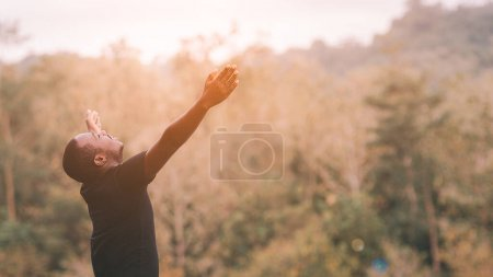 Libertad hombre africano es relajarse en la naturaleza verde con los ojos entrecerrados y levantado a los brazos del cielo en el día de verano soleado. Emoción sentirse bien y viajar concepto de aventura