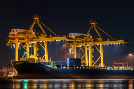 Photo for Container cargo freight ship with working crane bridge in shipyard at night for logistic import export - Royalty Free Image