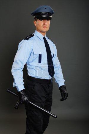 Photo pour Policier tient à portée de main la baton de police sur fond foncé - image libre de droit