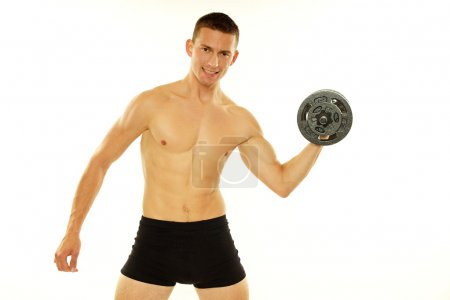 Athletic man poses with dumbbell