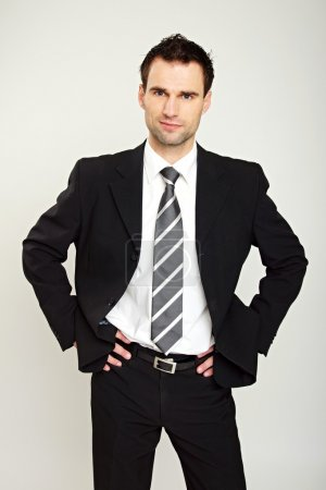 Photo for Portrait of handsome businessman in suit standing with hands on hips - Royalty Free Image