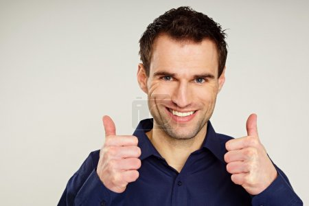 Handsome man gesturing thumbs up