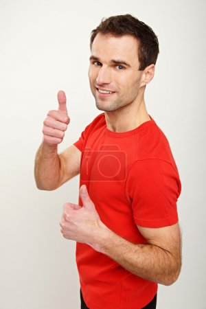 Photo for Portrait of handsome man in red shirt gesturing thumbs up sign on white background - Royalty Free Image