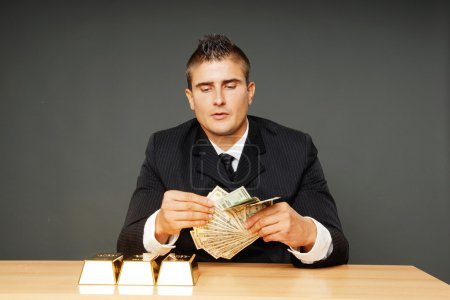 Man with gold bricks counts money