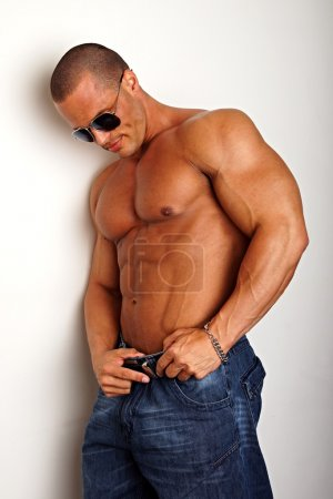 Photo for Handsome muscular man in sunglasses standing and posing - Royalty Free Image