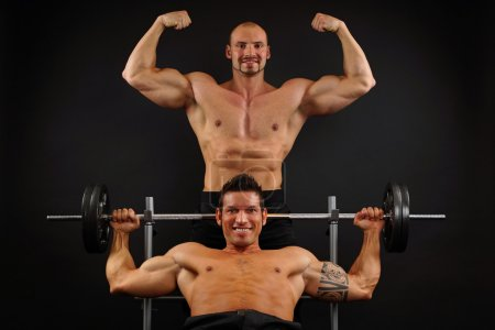 Photo for Two muscular men posing with dumbbells on dark background - Royalty Free Image