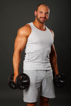 Muscular man poses with dumbbell