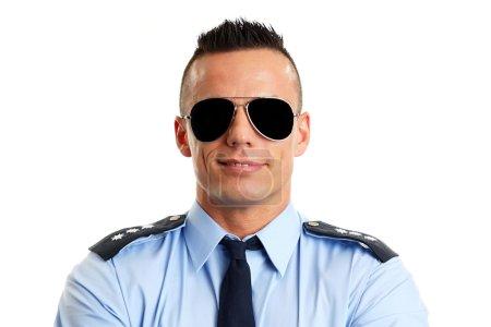 Photo pour Souriant policier en uniforme avec lunettes de soleil - image libre de droit