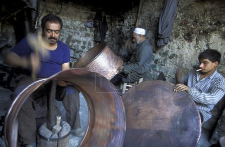 Craftsmen working with traditional brass dishes