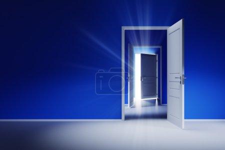 Three open white doors on the blue wall. Rays of light shine through the open door.