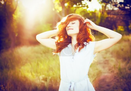 Photo for Emotional portrait of happy beautiful woman with red curly hair and natural makeup enjoying her life in nature. Soft sunny colors. Outdoor shot. Copyspace. - Royalty Free Image