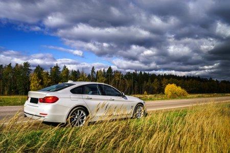Photo pour Voiture de luxe blanche et couleurs d'automne, nature vs technique - image libre de droit