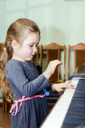 Cute little girl playing grand piano in music scho...