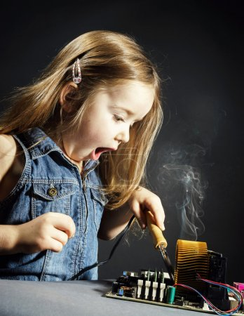 Foto de Cute little girl helping father to repair old computer motherboard using solderer - Imagen libre de derechos