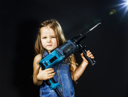 Foto de Cute little girl with drilling machine in her hands ready to professional constructing work - Imagen libre de derechos