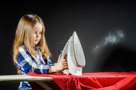Cute little girl helping your mother by ironing clothes, contras