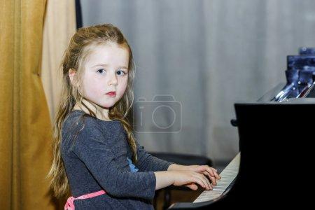 Cute little girl playing grand piano